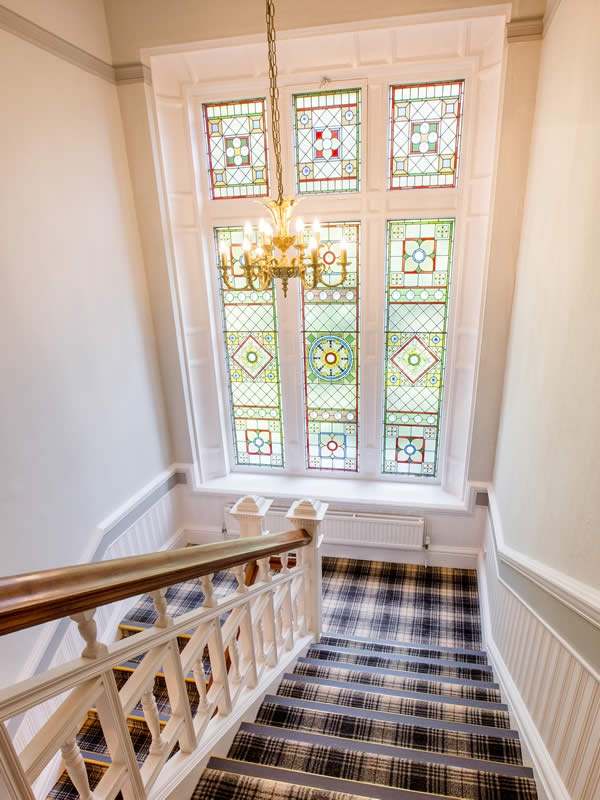 The stunning Victorian stained glass window creates beautiful light on the stair
